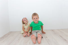 Beautiful boy and girl sitting on the floor Royalty Free Stock Photos
