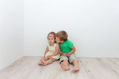 Beautiful boy and girl sitting on the floor and hugging Stock Photo