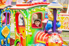 Beautiful boy having fun on the ride at the amusement park Stock Photography