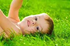 Beautiful boy lying on the grass Royalty Free Stock Image