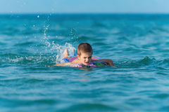 Beautiful boy making splashes in the middle of sea swimming Stock Photos