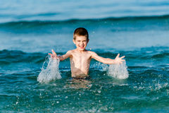 Beautiful boy making splashes in the middle of sea waves Stock Image
