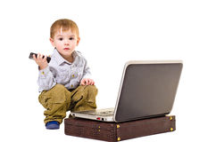Beautiful boy sitting next to a laptop. Beautiful boy with a mobile phone is sitting next to a laptop Royalty Free Stock Images