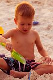 Beautiful boy play with shovel on a sand beach. Outdoors Royalty Free Stock Photos