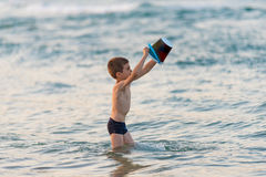 Beautiful boy playing with a bucket toy in the sea Stock Image