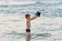 Beautiful boy playing with a bucket toy in the sea Stock Photography