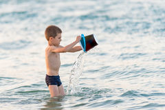 Beautiful boy playing with a bucket toy in the sea Stock Photos