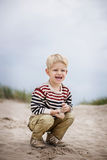 Beautiful boy playing with sand on the beach. Oudoor portrait Stock Photos
