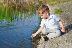 Beautiful boy pours water from the palm. Small beautiful boy pours water from the palm on the river Royalty Free Stock Photos