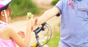 Beautiful teenage boy in protective bicycle helmet and girl in a park, boy giving flowers to the girl. Friendship. Beautiful boy in protective bicycle helmet and royalty free stock photo