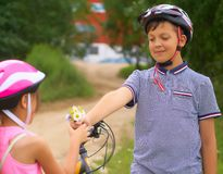 Beautiful teenage boy in protective bicycle helmet and girl in a park, boy giving flowers to the girl. Friendship. Beautiful boy in protective bicycle helmet and royalty free stock photography