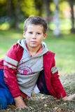 Beautiful boy in red jacket looking at camera outdoors Stock Image