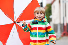 Beautiful boy with red umbrella and colorful jacket outdoors at Royalty Free Stock Image