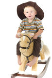Beautiful boy rides rocking horse Royalty Free Stock Photography