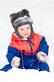 Beautiful boy sitting on the snow Royalty Free Stock Photos