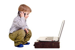 Beautiful boy speaks on the phone. Looking at laptop Royalty Free Stock Photography