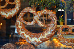 Beautiful Braided German Pretzels. Beautiful braided soft German pretzels hanging in a bakery in Germany. (In the background can be seen Schneeballen--snowballs royalty free stock photo
