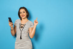 Beautiful Brazilian girl enjoying music with the head phones in. Blue background Royalty Free Stock Photography