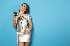 Beautiful Brazilian girl enjoying music with the head phones in. Blue background Royalty Free Stock Images