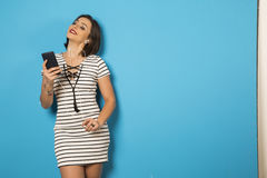 Beautiful Brazilian girl enjoying music with the head phones in. Blue background Stock Images