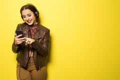 Beautiful Brazilian girl enjoying music with the head phones in. Yellow background Stock Images