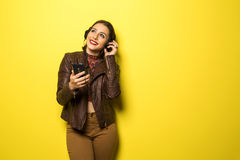 Beautiful Brazilian girl enjoying music with the head phones in. Yellow background Stock Photo