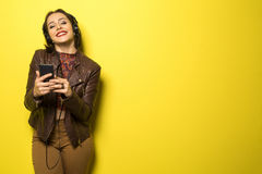 Beautiful Brazilian girl enjoying music with the head phones in. Yellow background Stock Photos