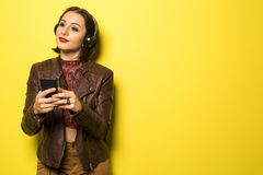 Beautiful Brazilian girl enjoying music with the head phones in. Yellow background Royalty Free Stock Photos