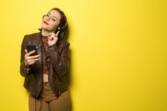 Beautiful Brazilian girl enjoying music with the head phones in. Yellow background Stock Photography