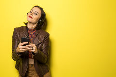 Beautiful Brazilian girl enjoying music with the head phones in. Yellow background Royalty Free Stock Images