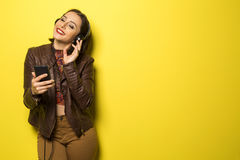 Beautiful Brazilian girl enjoying music with the head phones in. Yellow background Royalty Free Stock Photography