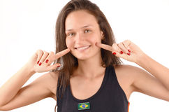 Beautiful Brazilian girl smiling. Attractive girl pointing to her beautiful smile. Happy Brazilian girl. Isolated on white background Royalty Free Stock Image