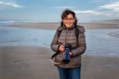 Beautiful middle-aged woman with glasses holding a camera on the beach, smiling and looking at the camera royalty free stock image