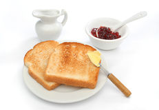 A beautiful breakfast scene. Two toast on a plate with butter on a knife and red jam behind. Deliciuos food for breakfast.  Look at my gallery for more meals Stock Photography