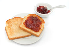 A beautiful breakfast scene. Two toast on a plate with red jam behind. Deliciuos food for breakfast. All white. Look at my gallery for more meals Royalty Free Stock Photo