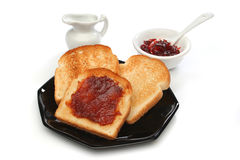 A beautiful breakfast scene. Three toast on a black plate with red jam behind. White background. Deliciuos food for breakfast.  Look at my gallery for more meals Royalty Free Stock Image