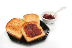 A beautiful breakfast scene. Three toast on a plate with  red jam behind. Deliciuos food for breakfast. White background.  Look at my gallery for more meals Royalty Free Stock Photos