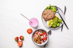 Beautiful breakfast: smoothie bowl, avocado toast and dessert on a white marble background, top view royalty free stock image