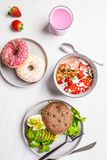 Beautiful breakfast: smoothie bowl, avocado toast and dessert on a white marble background, top view. Valentine`s Day concept stock image