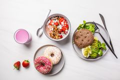 Beautiful breakfast: smoothie bowl, avocado toast and dessert on a white marble background, top view. Valentine`s Day concept stock photography