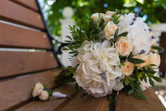 Beautiful bridal bouquet and boutonniere on a wooden bench. Beautiful wedding bouquet of roses and hydrangeas and boutonniere lie on a wooden bench Royalty Free Stock Photo