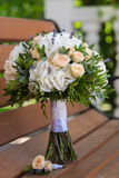 Beautiful bridal bouquet and boutonniere on a wooden bench. Beautiful wedding bouquet of roses and hydrangeas and boutonniere lie on a wooden bench Stock Image