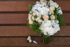 Beautiful bridal bouquet and boutonniere on a wooden bench. Beautiful wedding bouquet of roses and hydrangeas and boutonniere lie on a wooden bench Royalty Free Stock Photos