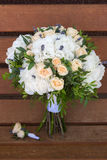 Beautiful bridal bouquet and boutonniere on a wooden bench. Beautiful wedding bouquet of roses and hydrangeas and boutonniere lie on a wooden bench Stock Photos