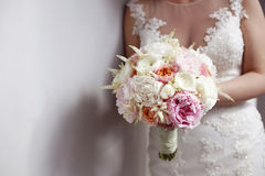 Beautiful bridal bouquet in bride's hands next to white wall Stock Photos