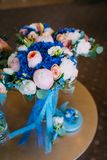 Beautiful bridal bouquet with creamy roses and peonies and blue hydrangeas. Wedding morning. Close-up Stock Image