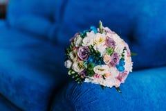 Beautiful bridal bouquet on deep blue sofa. Wedding concept Stock Photos