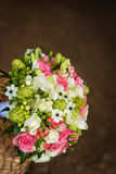 Beautiful bridal bouquet with golden rings in basket Royalty Free Stock Photo
