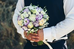 Beautiful bridal bouquet in hands of the groom. Wedding bouquet of white roses, hypericum, lisianthus, chrysanthemum, eustoma Stock Images