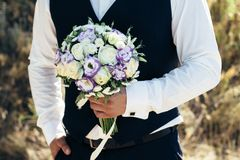 Beautiful bridal bouquet in hands of the groom. Wedding bouquet of white roses, hypericum, lisianthus, chrysanthemum, eustoma Royalty Free Stock Photography